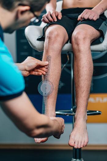 Man measuring male athlete leg in health club