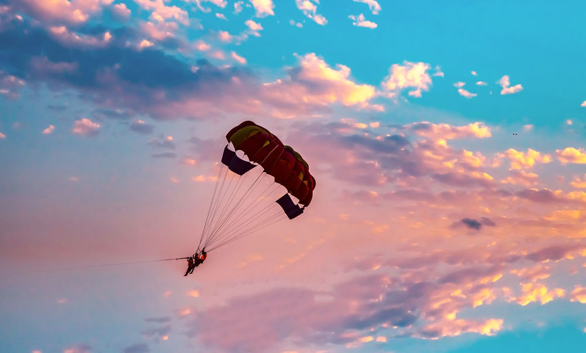 Low angle view of silhouette people parasailing against sky during sunset