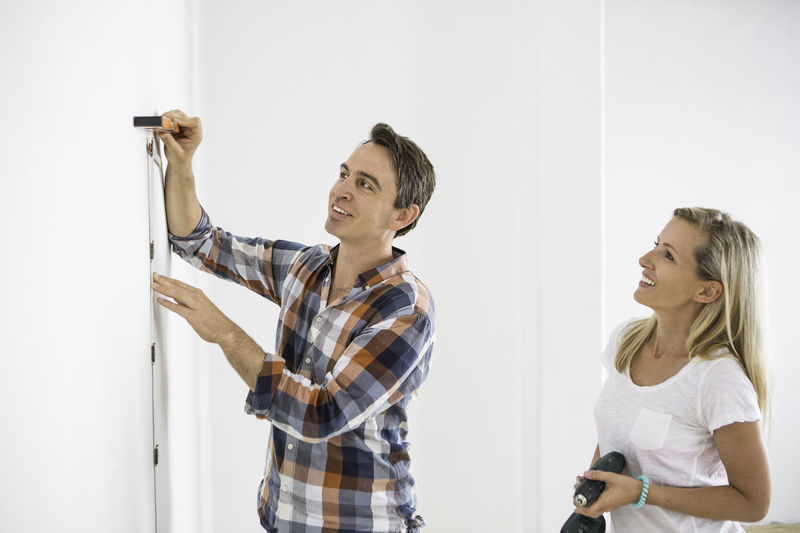 Man Measuring White Wall While Standing By Girlfriend At Home