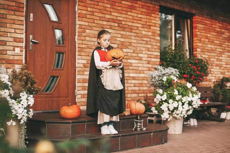 Full length of cute girl holding pumpkin standing against house