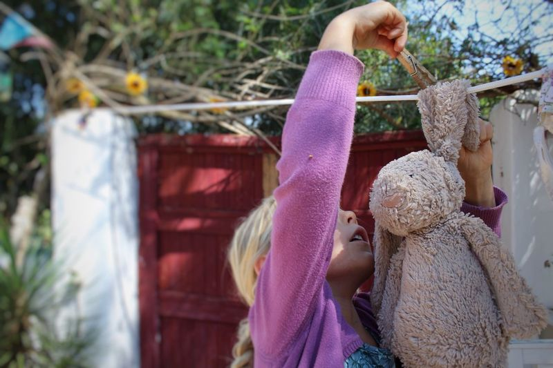 Girl Hanging Wet Bunny Toy On Clothesline