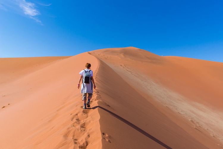 Tourist walking on the scenic dunes of Sossusvlei, Namib desert, Namib Naukluft National Park, Namibia. Adventure and exploration in Africa. Keywords: Sand Dune,exploration,one person,hiking,looking at view,namib,desert,Landscape,walking,Sand,tourist,namibia,remote,dune,sossusvlei,Travel,adventure,Scenics,sesriem,africa,discovery,freedom,eco tourism,loneliness,Smooth,tracks,infinite,dunes,drought,Travel Destinations,pattern,dry,people,panoramic,ripple,wilderness area,day,solitude,Famous Place,Nature,Environment,outdoors,sky,arid,travel destination,hot,barren,wilderness,red Adult Adults Only Adventure Arid Climate Blue Clear Sky Day Desert Full Length Landscape Men Nature One Man Only One Person Only Men Outdoors People Rear View Remote Sand Sand Dune Scenics Sky Tourism Young Adult