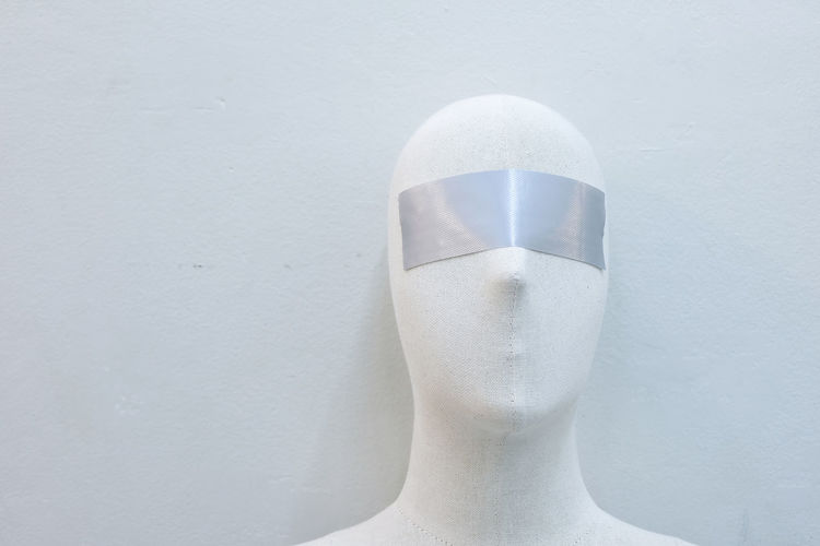 Close-up of mannequin with blind fold against wall