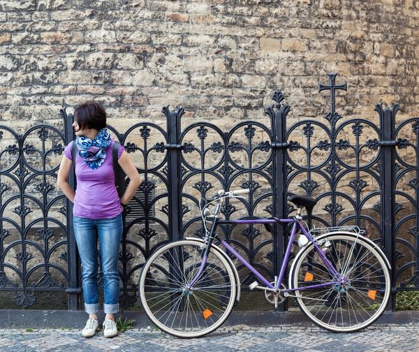 Woman with bicycle on sidewalk with wrought iron fence