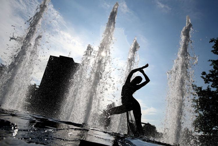 Water splashing in fountain against sky in city