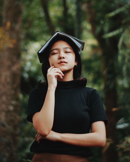 Young woman wearing hat standing in forest
