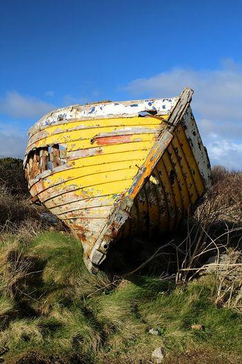 Abandoned boat against blue sky