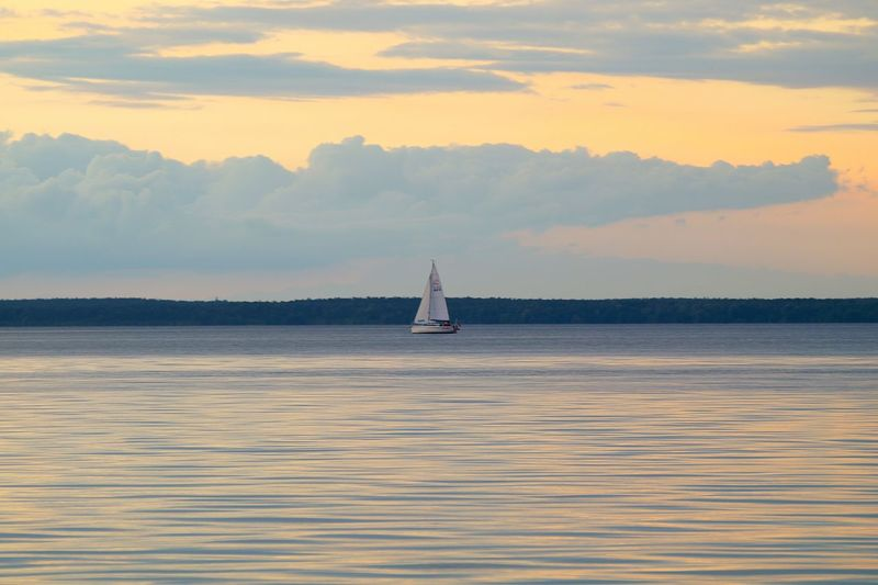 Boat Sailing In Sea At Sunset
