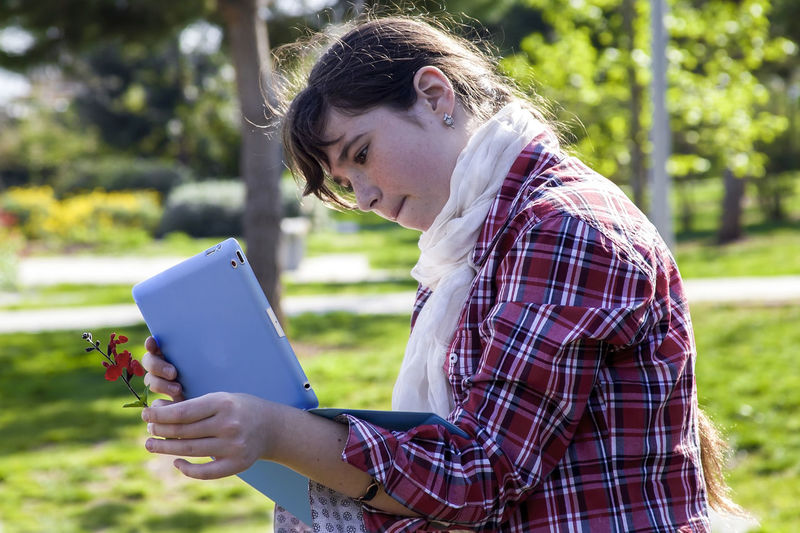 Casual teenage girl in plaid shirt and scarf using tablet and taking picture of small spring flower in sunlight One Person Holding Casual Clothing Leisure Activity Young Adult Lifestyles Real People Day Nature Side View Plant Sunlight Hairstyle Outdoors Girl Tablet Using Technology Photography Teenager Teenage Girl Springtime Sunny Day