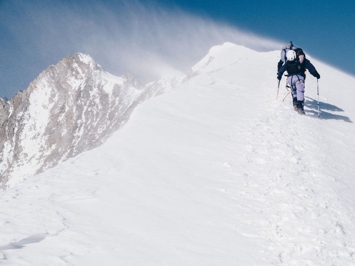 Low Angle View Of Hikers Walking On Snowcapped Mountain Against Clear Sky