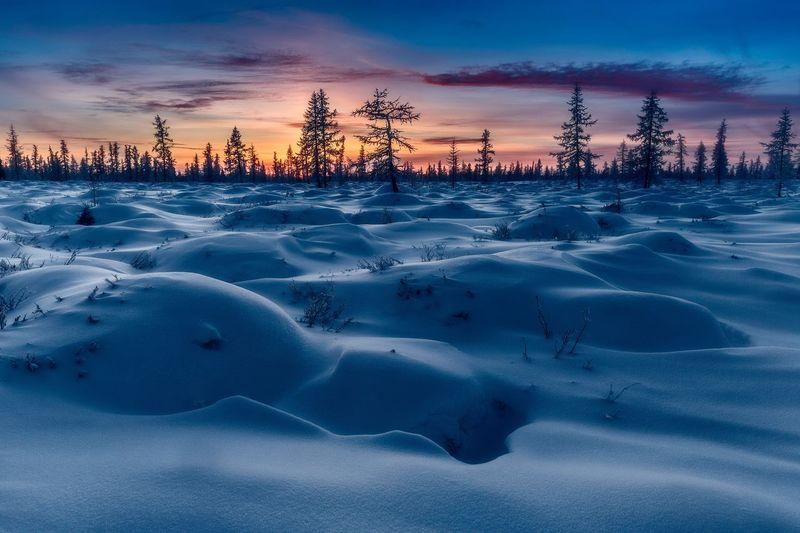 Frozen landscape against sky during sunset