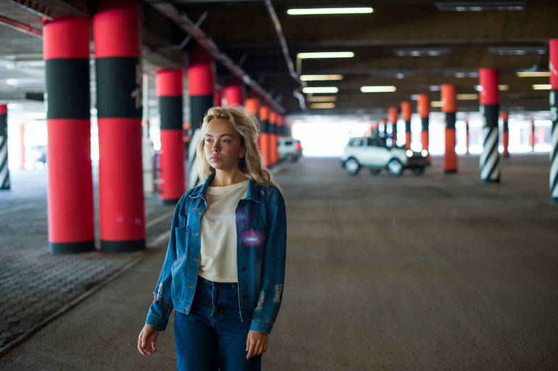 young beautiful woman in jeans clothes in parking of shopping center. Architectural Column Blond Hair Casual Clothing Day Focus On Foreground Front View Illuminated Indoors  Lifestyles One Person Parking Garage People Real People Standing Technology Transportation Young Adult Young Women