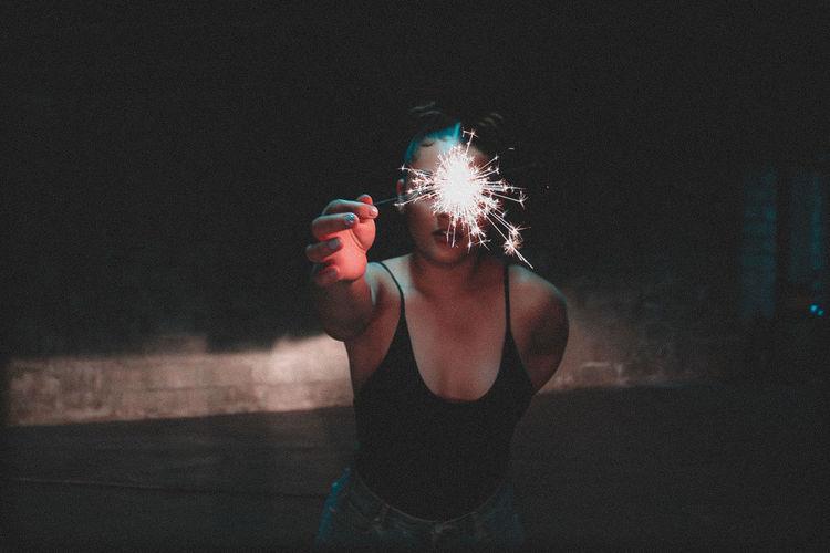 Woman holding illuminated light painting at night