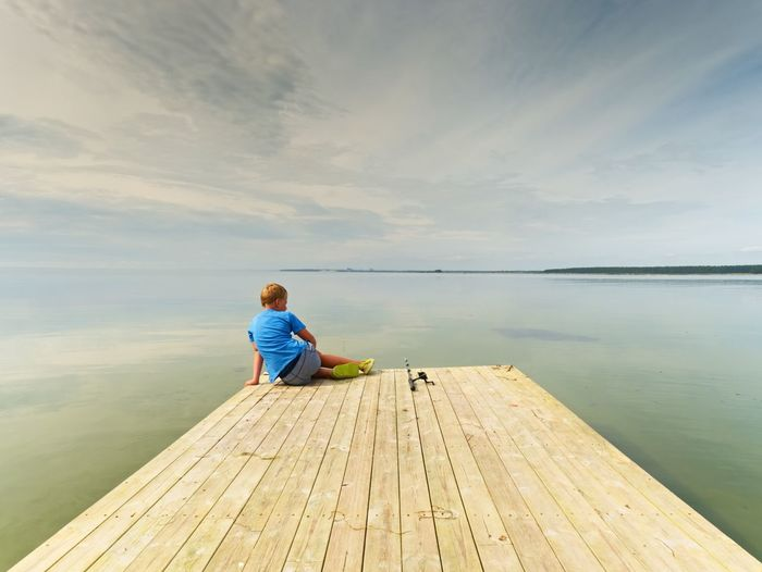 Small fisher on mole. blond boy in blue t-shirt, grey shorts and green flip-flops fishing on pier