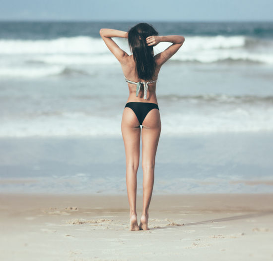 Full Length Rear View Of Beautiful Woman Standing At Beach