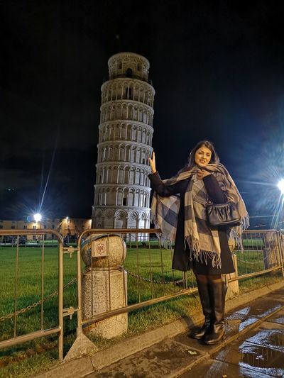 Optical illusion of woman standing against illuminated pisa tower