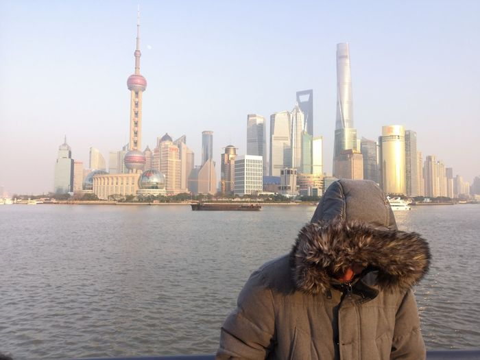 Man wearing warm clothing standing by river against modern buildings in city