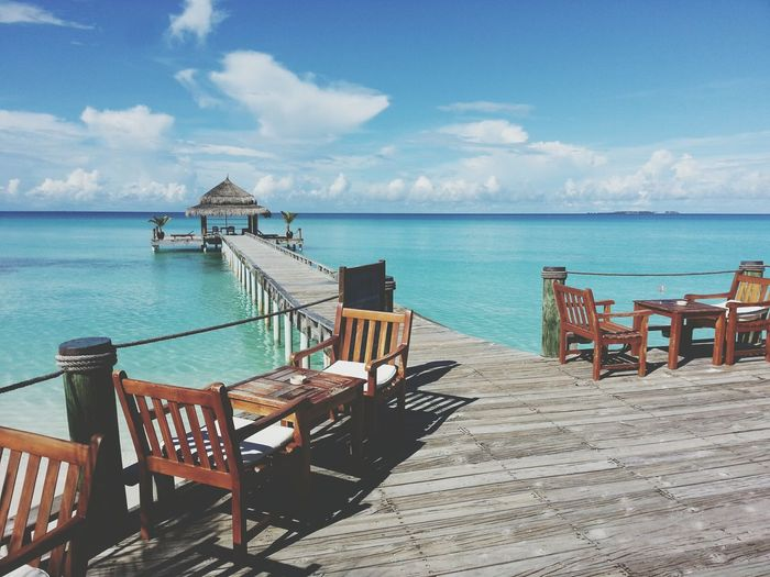 Empty chairs and tables on pier leading towards gazebo in sea against sky during sunny day