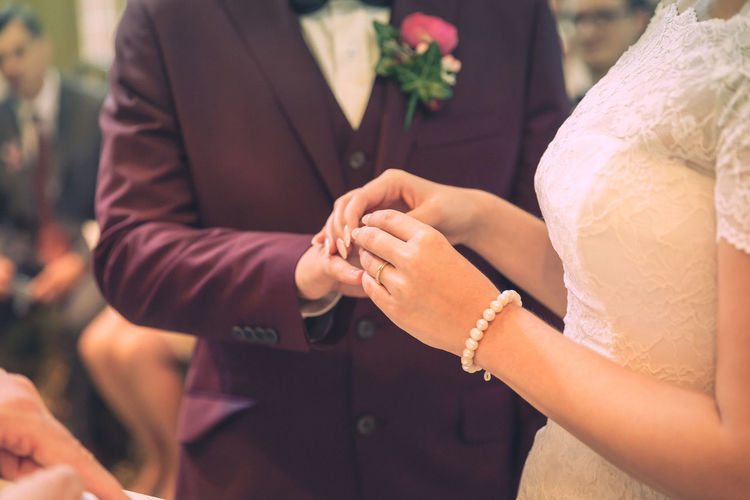 Midsection Of Bride Putting Ring In Groom Finger Indoors