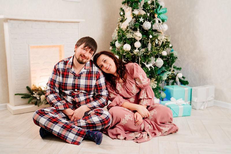 Young couple sitting on christmas tree