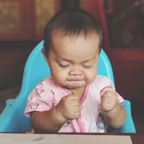 Close-up of cute baby girl making face while sitting on high chair at home