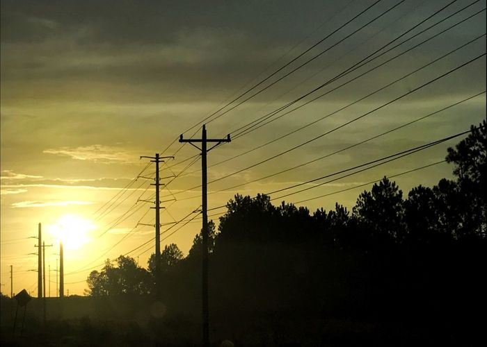 Morning sun rising over power lines and tree line. Energy Old Technology History Morning Sunrise Industry Modernization Electricity  Power Line  Sky Sunset Technology Cable Electricity  Silhouette Connection Electricity Pylon Power Supply Power Line  Low Angle View No People Fuel And Power Generation Tree Nature Plant Cloud - Sky Orange Color Outdoors Beauty In Nature