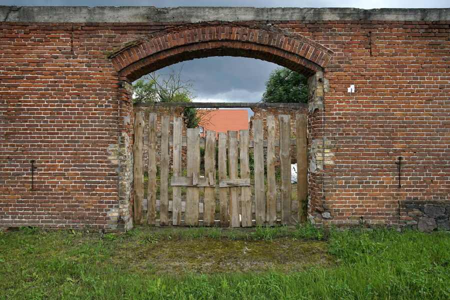 Abandoned Arch Architecture Barn Brick Wall Building Exterior Built Structure Closed Day Door Grass History Nature No People Old Ruin Outdoors