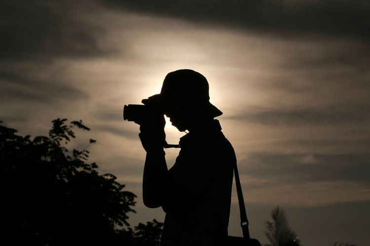Side View Of Silhouette Young Man Photographing Against Sky During Sunset