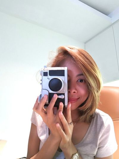 Portrait of smiling mid adult woman photographing with camera at home