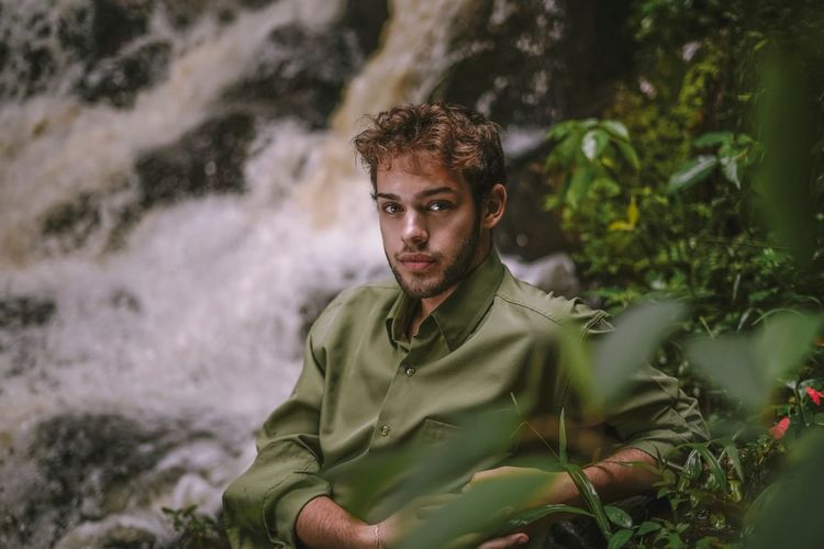 Portrait of man sitting on rock against waterfall