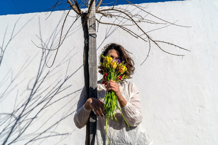 Silhouette woman standing by flowering plant against bare tree