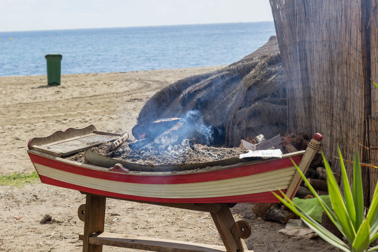 Firewood burning in boat at beach