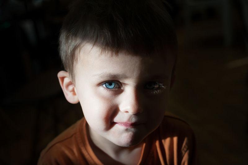 Close-up portrait of cute boy in darkroom