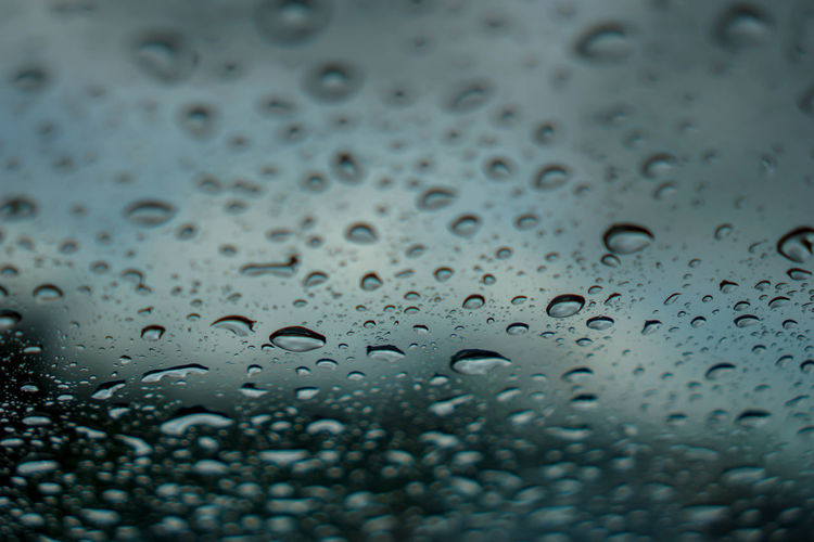 blur backgruond,Rain water on the car glass Drop Wet Rain Water Glass - Material Full Frame Transparent Window RainDrop Backgrounds Close-up No People Indoors  Selective Focus Rainy Season Nature Day Pattern Glass