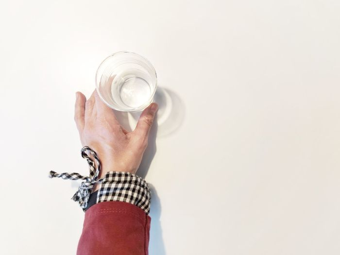 Midsection of man holding glass against white background