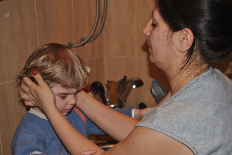 Mother covering ears of son in kitchen