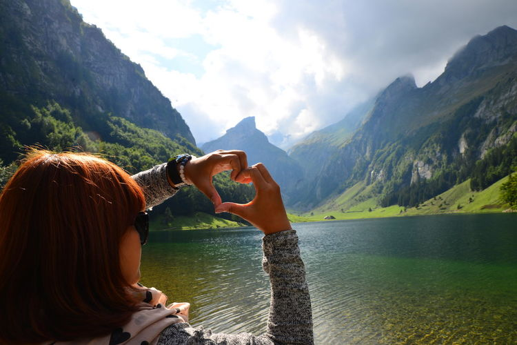Rear view of woman making heart shape with hands over lake against mountains and sky