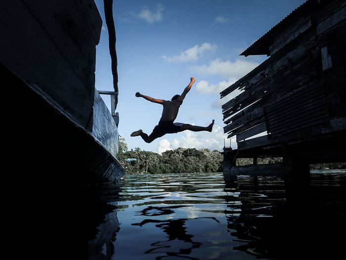 Woman jumping in water against sky