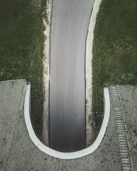 Directly above shot of empty road by trees in city