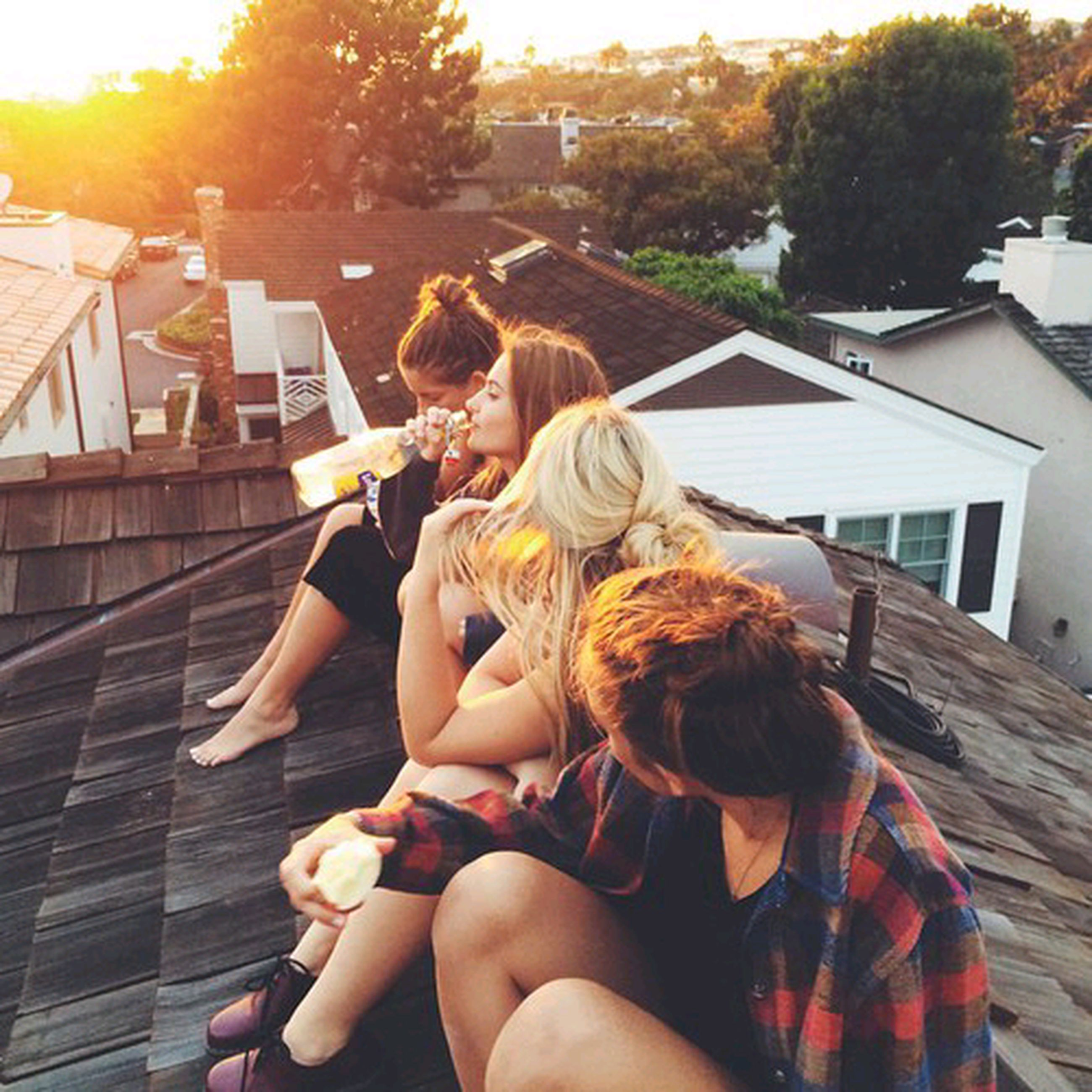 lifestyles, leisure activity, person, tree, casual clothing, young adult, sitting, childhood, building exterior, young women, built structure, holding, sunlight, architecture, full length, girls, relaxation, elementary age