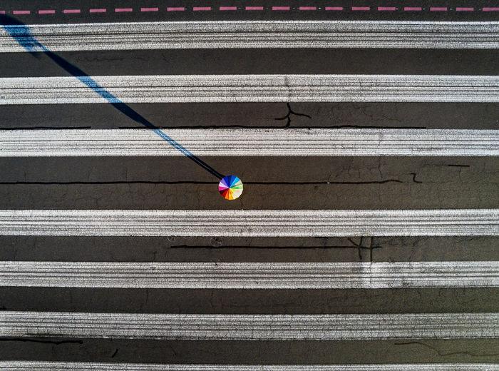 Umbrella and stripes. Umbrella Regenschirm Regenbogen Regenbogenfarbe Rainbow Colors Diversity Diversitat Streifen Zebrastreifen Sonnenaufgang Schattenspiel  Schatten Shadow Shades of Winter Asphalt Tempelhofer Feld Berlin Berliner Ansichten Drone  Dronephotography Drohnenbild Zebra Crossing