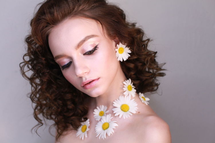 Close-up of teenage girl wearing flowers against wall