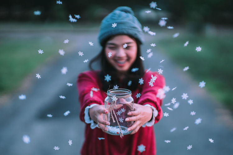 Hello, December make my wish come true. ❄🎅🎄. Young smiling woman throwing snowflakes with blurry background. Water Nature Women Glass Portrait Happiness Celebration Snow Christmas Outdoors Smiling Christmas Lights Christmas Decoration Snowing Emotion Snow ❄ Refreshment Holding Front View Lifestyles Looking At Camera One Person Casual Clothing Leisure Activity Snowcapped Mountain