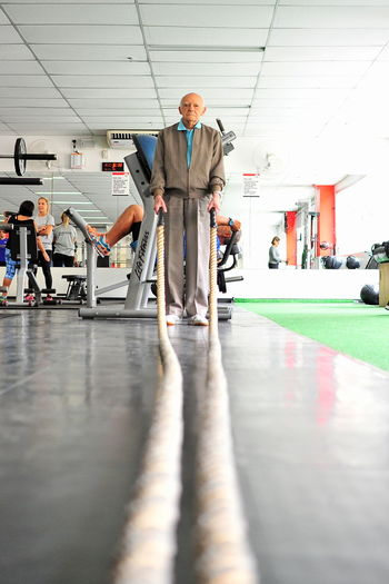 Full Length Portrait Of Man Holding Rope While Standing In Gym