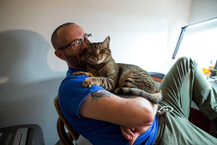 Midsection of man with cat at home