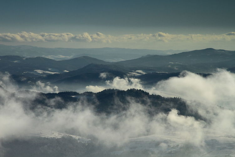 Scenic view of cloud covered mountains against clear sky