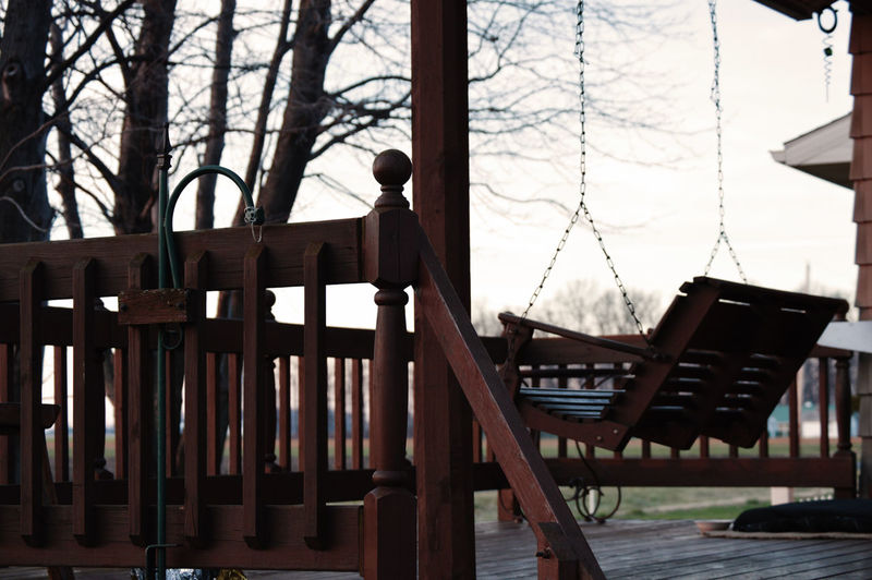 Wooden swing at patio against sky