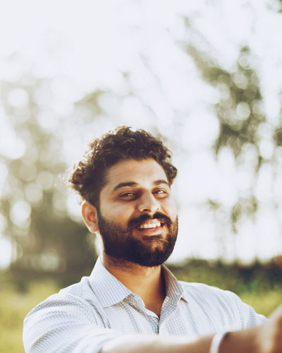 Portrait of bearded smiling young man outdoors