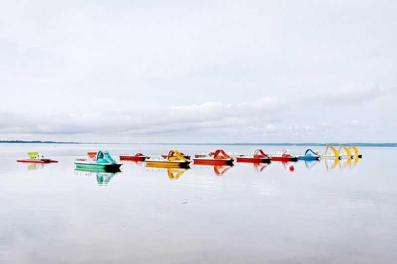 Colorful pedal boats on sea against sky
