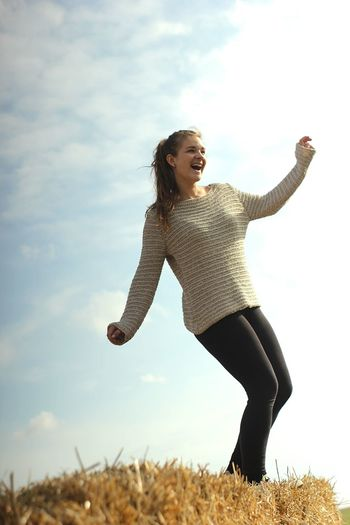 Low Angle View Of Happy Young Woman On Haystack Against Sky